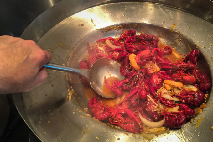 Step 2: A quick turn in a wok layers on the buttery, garlic-infused sauce of my Two-Step Boiled Louisiana Crawfish.